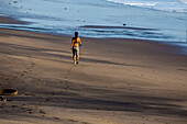 Young asian girl runs on the beach in Bali, Indonesia