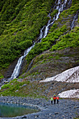 Group Of People Walking Along The Shoreline In Front Of A Waterfall, Shoup Bay State Marine Park, Prince William Sound, Alaska