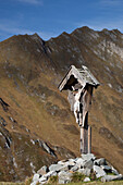 'Wooden crucifix memorial on grassy slope with mountain range and blue sky in the background; Hintertux, Austria'