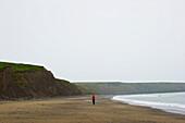 'A man walks alone on a Aberdaron Beach; Wales'
