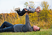'Father holding his son high in the air pretending to fly; Edmonton, Alberta, Canada'