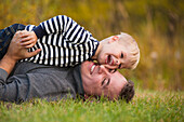 'Father playing with his young son on the grass in a park in autumn; Edmonton, Alberta, Canada'