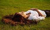 'Portrait of a young woman with long red hair laying in the grass; Edmonton, Alberta, Canada'