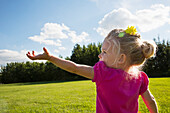 'A young girl reaching up to the sky in a park; St. Albert, Alberta, Canada'