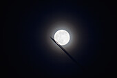 'Commercial jet leaves a vapor trail as it flies past the full moon; Prescott, Arizona, United States of America'
