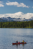 'Two women and young girl in a red canoe on Byers lake with green forested shoreline and Mount McKinley peaking through the clouds, Denali State Park; Alaska, United States of America'