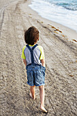 'Young boy walking on the beach; Hollywood, Florida, United States of America'