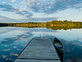 'A canoe tied to a wooden dock and clouds reflected in a tranquil lake; Ontario, Canada'