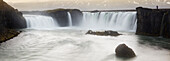 'Panoramic view of Gooafoss waterfall, with photographer standing on edge showing it's scale; Iceland'