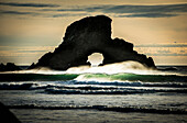 'Surf breaks near a natural arch; Cannon Beach, Oregon, United States of America'