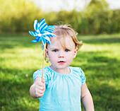 'Young girl with pinwheel in a park; Edmonton, Alberta, Canada'