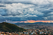 'The skies turn stormy over the skies of Cochabamba, with El Cristo seen on the mountain in the middle of the city; Bolivia'