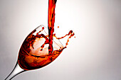 'Close up of red wine being poured into a wine glass and splashing out; Calgary, Alberta, Canada'
