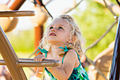 'Young girl climbing a ladder in a playground; Spruce Grove, Alberta, Canada'