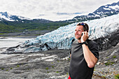 'Man talking on a cell phone in front of Shoup glacier, Shoup Bay State Marine Park, Prince William Sound; Valdez, Alaska, United States of America'