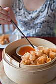 Woman eating prawn wrapped in fried rice paper at The Waterfront restaurant, Da Nang, Vietnam, Indochina, Southeast Asia, Asia