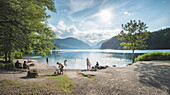 Lake Alpsee near Castle Neuschwanstein and Fuessen town with people enjoying leisure activities, Bavaria, Germany, Europe