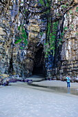 Woman looking at the giant entrance of the Cathedral caves, The Catlins, South Island, New Zealand, Pacific