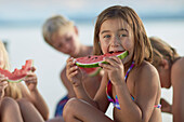 Girl eating a slice of melon, lake Starnberg, Upper Bavaria, Bavaria, Germany