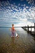 Boy with toy sail boat standing in lake Starnberg, Upper Bavaria, Bavaria, Germany