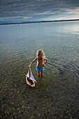 Girl with a toy sailboat in lake Starnberg, Upper Bavaria, Bavaria, Germany
