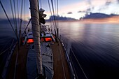Sailing boat, yacht with night lighting system in the dusk, Sailing