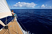 Yachtsman sitting on the bow of a sailing yacht in the Caribbean Sea