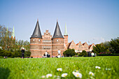 Holsten Gate with salt storehouses and churches of St. Peter and St. Mary in background, Lubeck, Schleswig-Holstein, Germany