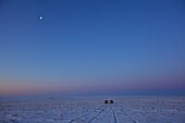 two UAZ buses in the Mongolian steppe in wintertime, with half-moon in the sky, Mongolia