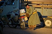 Mongolian man with motorcycle in traditional winter clothes, Mongolia