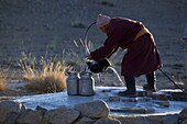 Monk getting water out of a well in the Amarbuyant monastery in winter, Mongolia