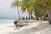 Group of Kuna Indians sitting in the palm grove on the sandy beach of San Blas Islands, Panama, Central America.