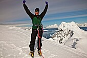 Female climber happy to have reached summit Mt Don Roberts, Lemaire Island, above Paradise Bay, Antarctic Peninsula.
