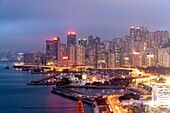 Skyline of Hong Kong Island with commercial and residential buildings with a conjested road in the foreground at dusk, China, East Asia