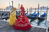 Two masked women at the carnival in Venice with gondolas in the background, Italy, Europe