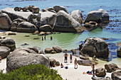 Tourist and locals enjoy protected shallow ocean water, Boulders Beach National Park, Simonstown, South Africa.