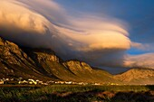 Landscape photo of a dramatic lenticular cloud sunset over the mountains of Bettys Bay. Bettys Bay, Western Cape, South Africa.
