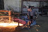 Factory worker using a steel-cutting machine in a brickyard, Ulaanbaatar, Mongolia