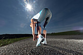 Female jogger doing up the shoelaces, Starnberger See, Bavaria, Germany