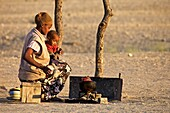 Herero woman with child cooking, Sesfontain, Namibia
