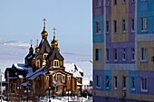 Orthodox Cathedral of the Holy Trinity next to coloured apartment house, Anadyr, Chukotka Autonomous Okrug, Siberia,  Russia