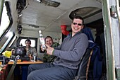 three men in the operator's cab of a tracked vehicle, one laughing at a bottle of vodka, Chukotka Autonomous Okrug, Siberia, Russia