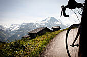 Cyclist on mountain pass, view to Eiger and Moench, Bussalp, Bernese Oberland, Switzerland