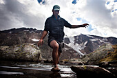 Man wading through a mountain lake, near Bremer Hut (ca. 2413 m), rear of Gschnitz Valley, Stubai Alps, Tyrol, Austria