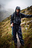 Man in rainy weather on a mountain trail, descent from Bremer Hut (2413 m), rear of Gschnitz Valley, Stubai Alps, Tyrol, Austria