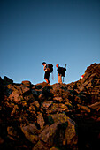 Hikers in rocks observing the sunrise, ascend to Habicht (3277 m), Stubai Alps, Tyrol, Austria