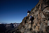 Two hikers climbing through rocks, ascend to Habicht (3277 m), Stubai Alps, Tyrol, Austria