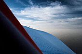 Mountaineer on glaciate mountain ridge, View from a tent, Mont Blanc Mountain Massif, Graian Alps, France
