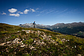 Hiker walking on mountain meadow, Monte die Glorenza (2395 m), Vinschgau, South Tyrol, Italy