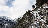 Hiker climbing over snow-covered rocks, ascend to Unnutz Mountain (2078 m), Rofan Mountains, Tyrol, Austria
